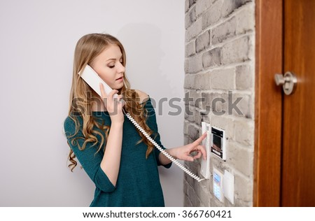 Woman talking on the intercom and presses the button to open the door - stock photo