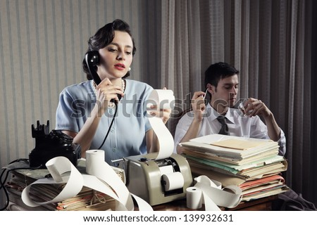 Woman talking on the phone calculating and analyzing financial reports, businessman relaxed in chair in the background - stock photo