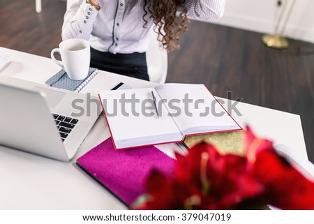 Woman talking on the phone, desk in first plan and her planer.  - stock photo