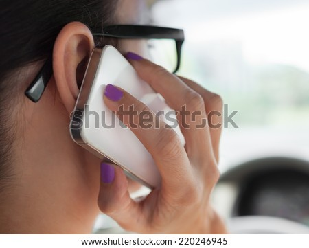 Woman talking on the phone while driving a car - stock photo