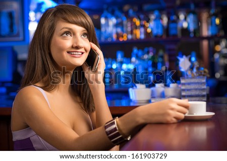 woman talking on the phone while sitting with a cup of coffee at the bar