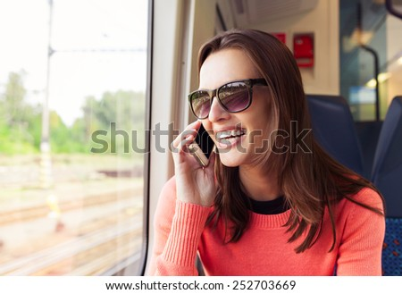 Woman talking on the phone while traveling by train - stock photo