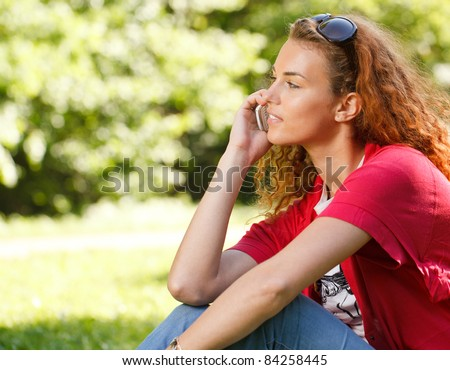 Woman talking over the phone in park - stock photo