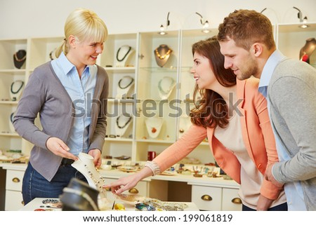 Woman talking to a salesperson at jeweler store - stock photo