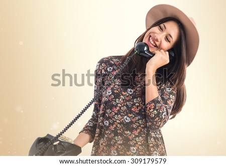 Woman talking to vintage phone over ocher background - stock photo