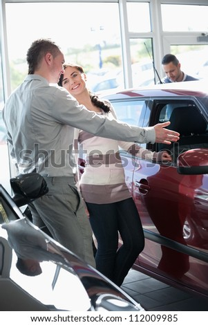 Woman talking with a salesman in a car shop - stock photo