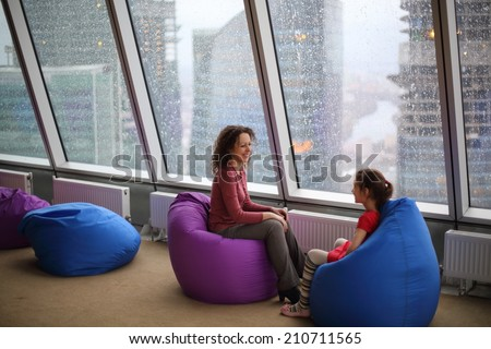 Woman talking with her daughter sitting on padded stools at the glass wall on a rainy day - stock photo