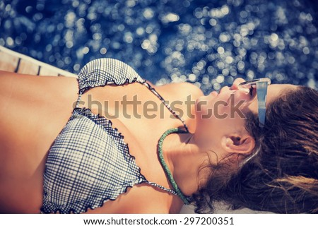 Woman tanning on the sailboat, wearing stylish swimsuit, lying down and relaxing on the board, enjoying bright sun light, spending summer vacation with pleasure  - stock photo