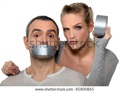Woman taping-up mans mouth - stock photo