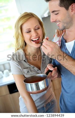 Woman tasting italian sauce cooked by boyfriend - stock photo