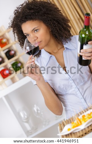 woman tasting wine in glass and holding bottle
