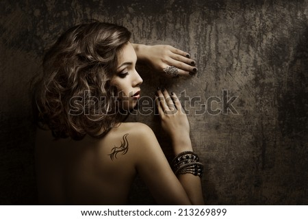 Woman Tattoo on back shoulder, sexy girl beauty fashion portrait over dark grunge background - stock photo
