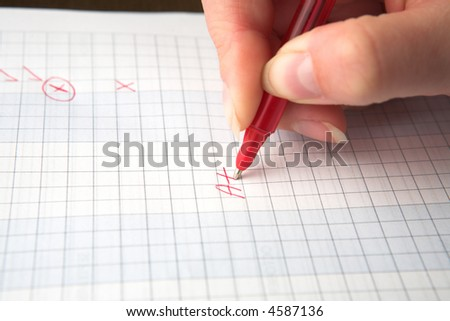 Woman teacher marking a test paper with an A+, holding a red pen, shallow depth of field with focus on the A. - stock photo