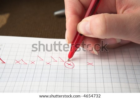 Woman teacher marking a test paper with crosses and check marks, shallow depth of filed focus on X
