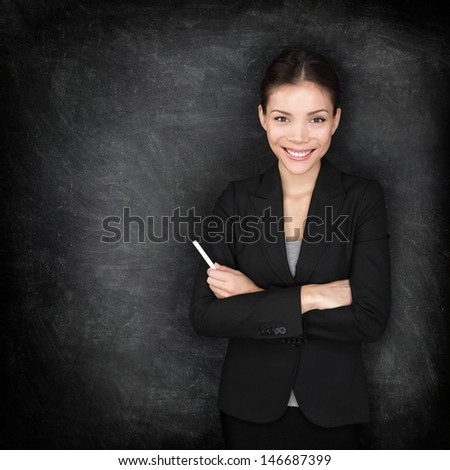 Woman teacher or business woman at blackboard holding chalk standing in suit by blackboard teaching or giving lecture. Young female professional portrait. Mixed race Asian Caucasian female model. - stock photo