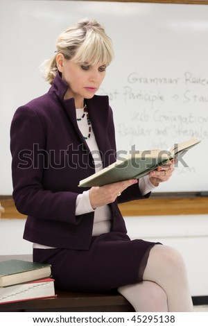 Woman teacher or instructor in a college, university, high school, middle school, elementary classroom sitting on her desk holding a book and reading. - stock photo