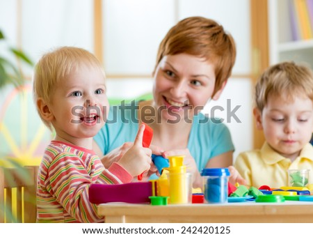 woman teaches children handcraft at kindergarten or playschool - stock photo