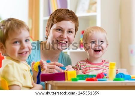 woman teaches children handcraft at kindergarten or playschool or home - stock photo