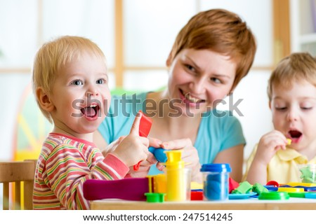 woman teaches kids handcraft at kindergarten or playschool - stock photo
