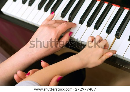 Woman teaches the child to play the piano. - stock photo