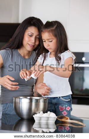 Woman teaching child to prepare dough with healthy ingredients - stock photo