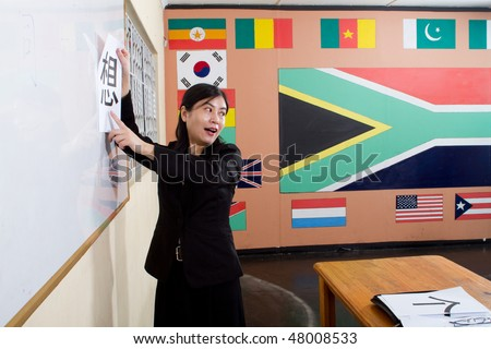 woman teaching chinese in classroom, background is various country flags