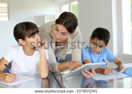 Woman teaching class to school children with digital tablet - stock photo