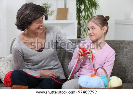 Woman teaching her granddaughter how to knit - stock photo