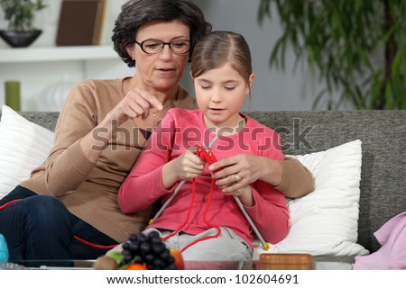 Woman teaching how to knit to little girl - stock photo