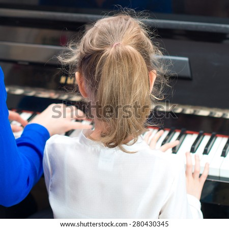 Woman teaching little girl to play the piano. Back view. - stock photo