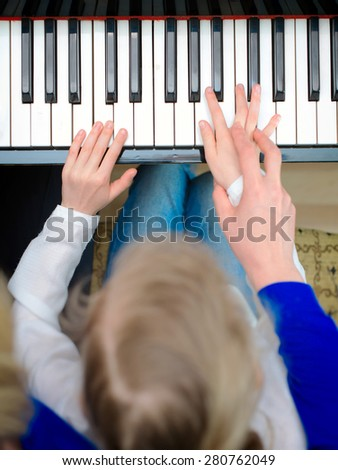 Woman teaching little girl to play the piano. Top view. - stock photo