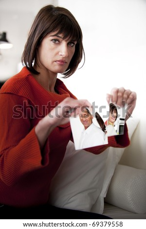 Woman Tearing Photograph of Her Relationship - stock photo