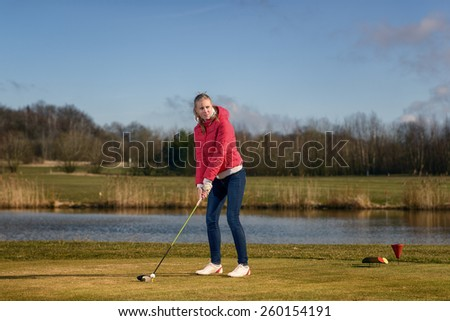 Woman teeing of on a golf course standing in the tee box in front of a water hazard with a driver in her hands ready to make a distance stroke - stock photo