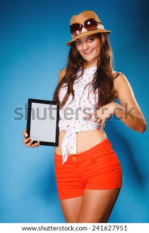 Woman teen girl showing blank copy space screen of tablet touchpad computer on blue. Electronic technology.