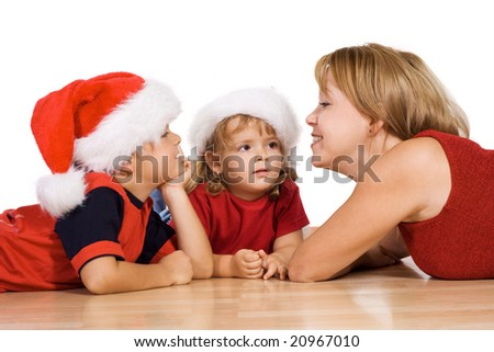 Woman telling a christmas story to her kids laying on the floor - isolated - stock photo