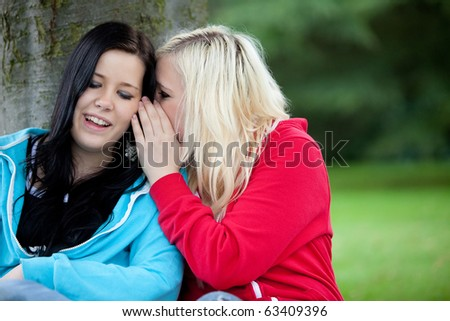 Woman telling a secret to her friend outdoors - stock photo