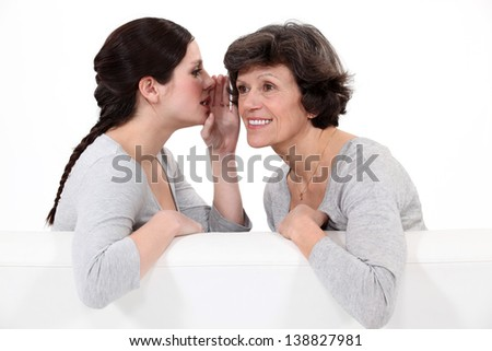 Woman telling her mother a secret - stock photo