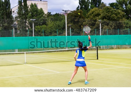 Woman tennis player in action wearing a sportswear during a match on a court outdoor in summer or spring