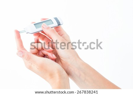 Woman testing her blood glucose level on white background