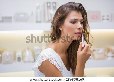 Woman testing lipstick at a beauty salon - stock photo