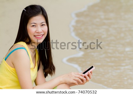 Woman text messaging on cell phone at beach.