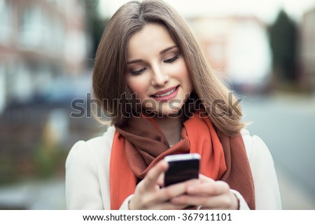 Woman texting. Closeup young happy smiling cheerful beautiful woman girl looking at mobile cell phone reading sending sms isolated cityscape outdoor background. Positive face expression human emotion - stock photo