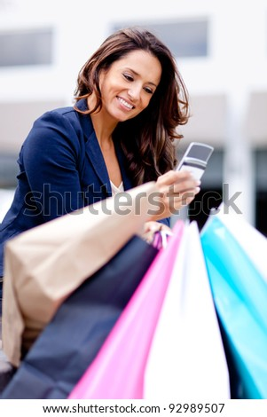 Woman texting on her cell phone while shopping - stock photo