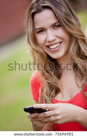 Woman texting on her mobile phone outdoors - stock photo