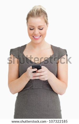 Woman texting on her smartphone against white background - stock photo