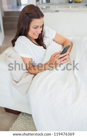 Woman texting with her mobile phone while lying on the sofa
