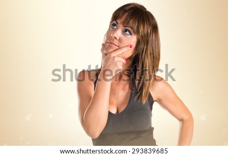 Woman thinking and looking up over ocher background - stock photo