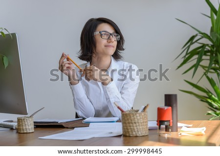 Woman thinking at her workplace - stock photo