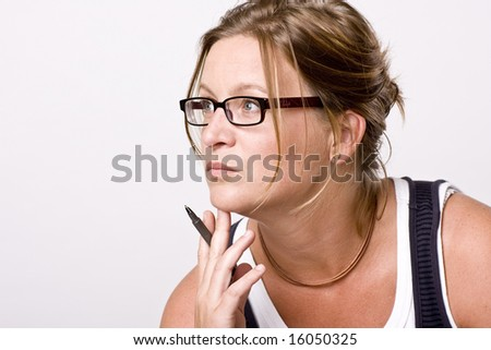 Woman thinking or listening. She is focused with a pencil in her hand - stock photo