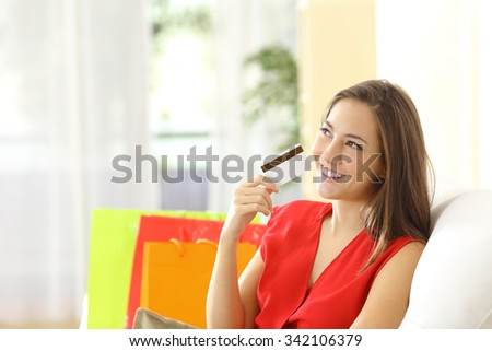 Woman thinking with credit card sitting on a couch with shopping bags at home - stock photo